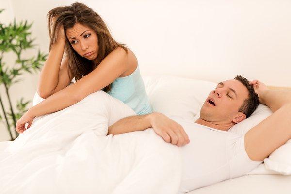 Mann schnarcht im Bett, die Frau sitzt verzweifelt daneben