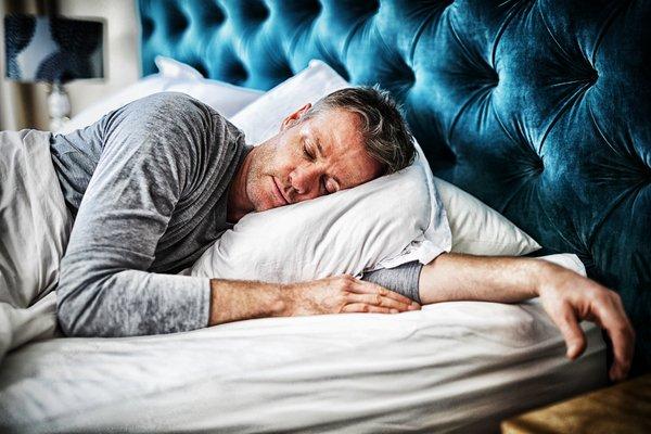 Mann schläft ruhig im Bett