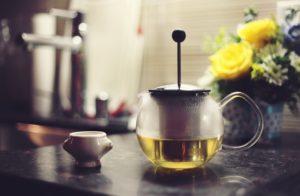 Teekanne aus Glas mit grünem Tee
